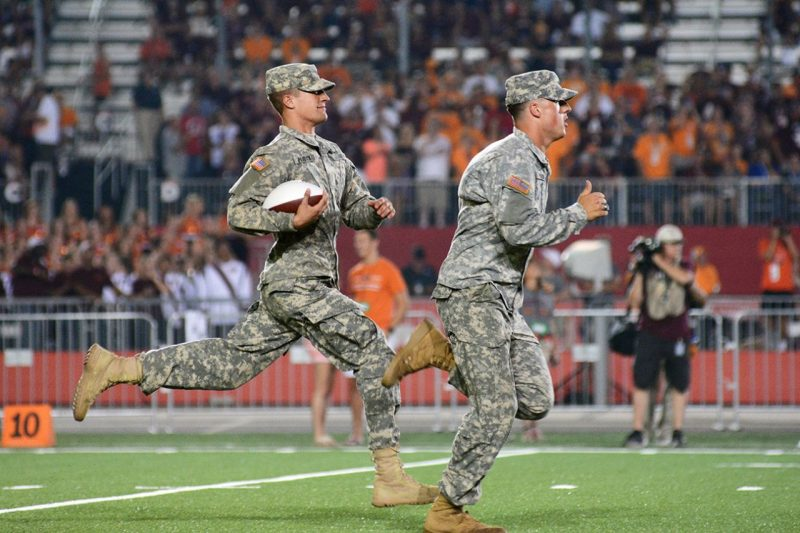 Cadets Cadet Stephen Pistoia '17 and Ben Paddock '17 run the game ball onto the field during the Battle at Bristol.
