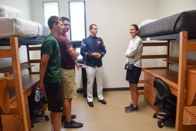 A cadet talks with a family inside a cadet room in New Cadet Hall.
