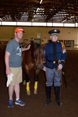 Outgoing cadet commander Anthony Clifton poses with his father and Laverne the horse.