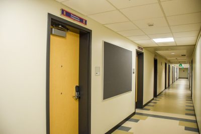 Commanders' rooms are clearly marked as you look down a hallway of New Cadet Hall.