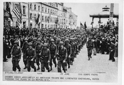 American troops march on a city street.