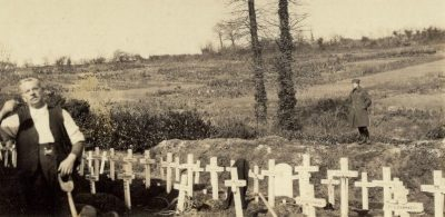 A man stands near grave markers.