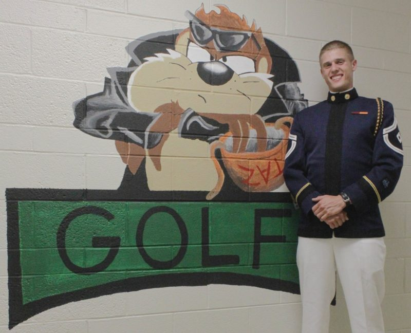 Cadet John Rogalo, the First Sergeant for Golf Company this fall standing in front of a mural in Golf Company