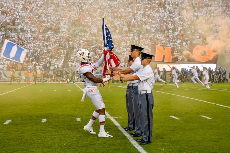 Cadets receive the flags from football players in Lane Stadium.