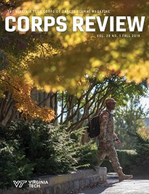 A cadet walks on a tree-lined sidewalk on the cover of the fall 2018 edition of the Corps Review magazine.