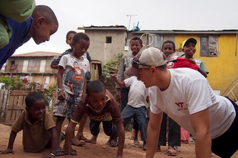 Cadet Jacob Moberly '19, at right, children how to do a pushup in Madagascar.