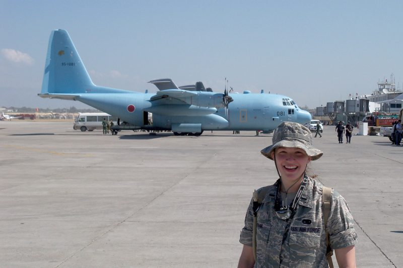 Maj. Susan Frank poses for a picture in Port-au-Prince, Haiti, after the 2010 earthquake. A Japanese C-130 is parked behind her.