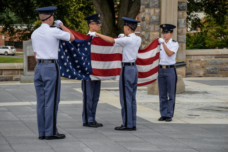Members of the Corps' Color Guard fold the American flag.