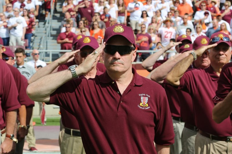 Gen. Carlton D. Everhart '83 salutes as the National Anthem is played during the Corps Homecoming football game.