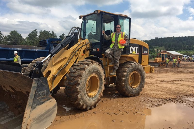 Eric Daly '16 stands on a bulldozer.