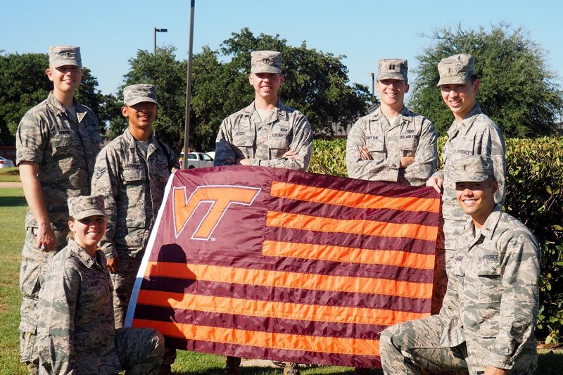 A group of soldiers holds a Virginia Tech flag.