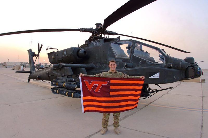 1st Lt. Jack Manning holds a Virginia Tech flag in front of a helicopter.