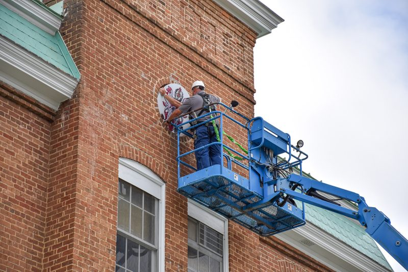University workers replace the weathered heraldry from Lane Hall with a new Corps shield done in metallic colors.