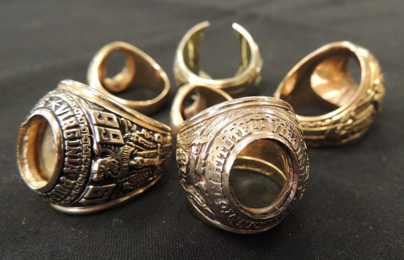 Six class rings with their stones removed sit in a circle.