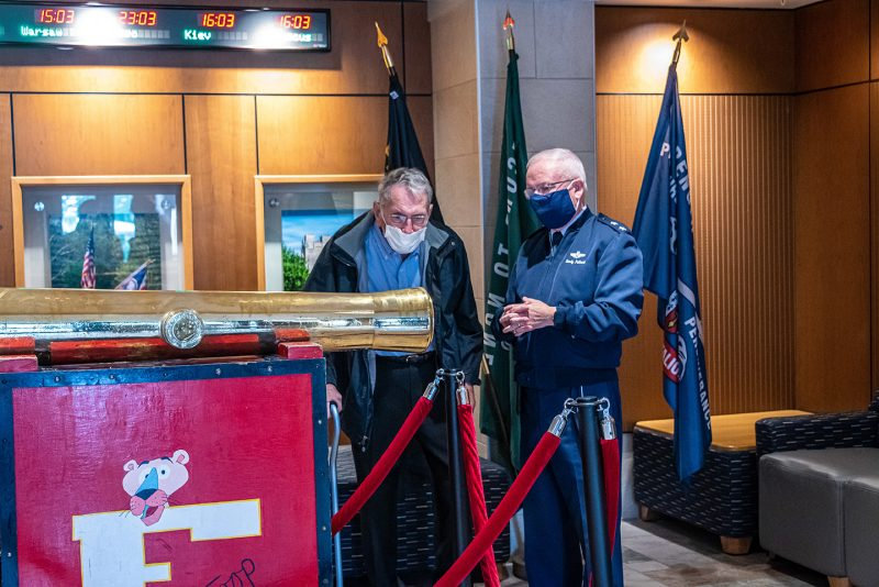 Sam Bickford '53 (left) takes a look at the original Skipper cannon in the lobby of Pearson Hall West during a tour of Upper Quad given by Maj. Gen. Randal Fullhart, commandant of cadets (right).