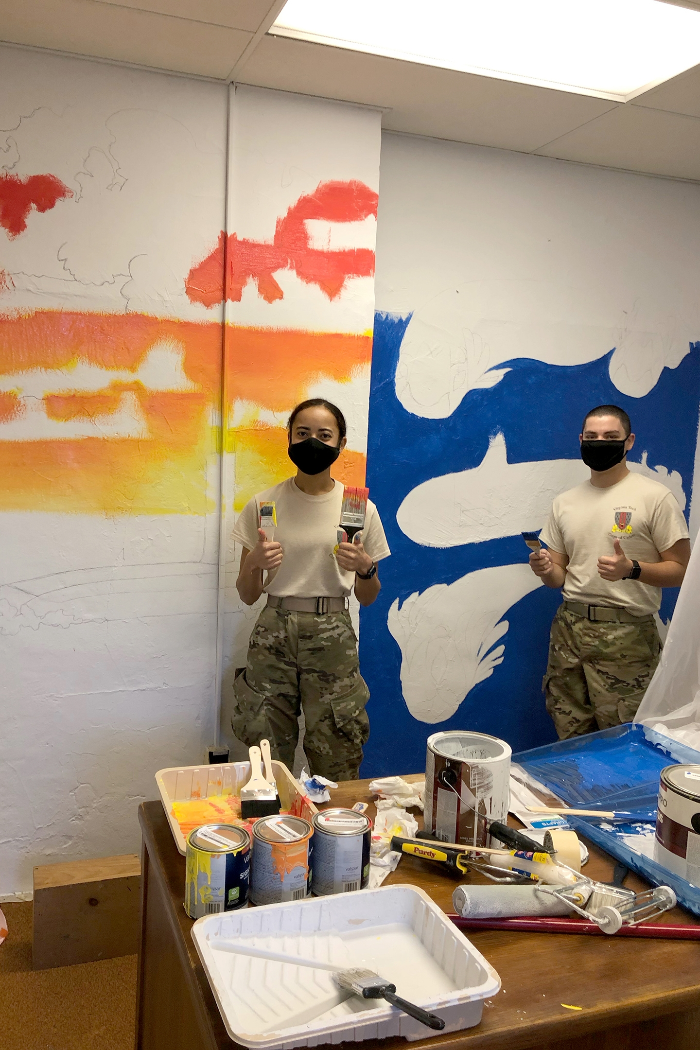 Midshipmen Ayana Bullock '22 (left) and Marc Mendez '24 paint the new midshipmen lounge in Lane Hall.