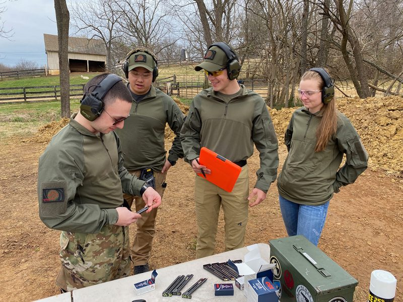 Four cadets practice at an outdoor shooting range.