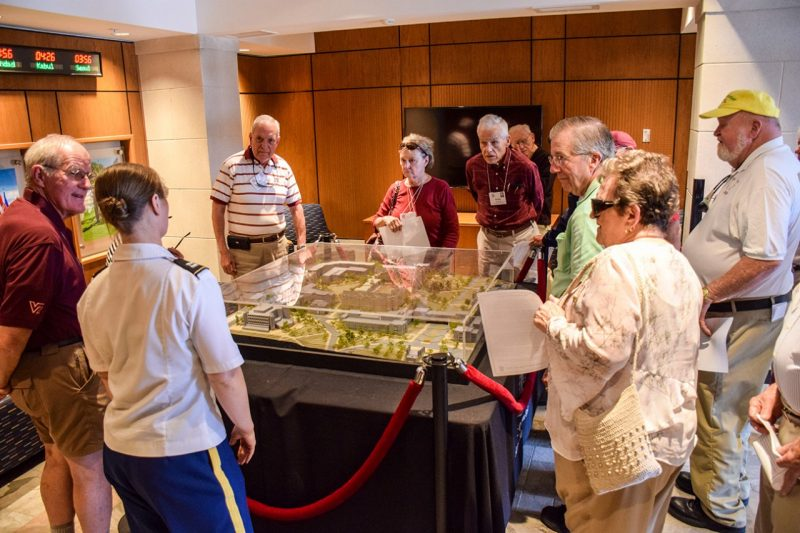 Alumni gather around a model of Upper Quad.