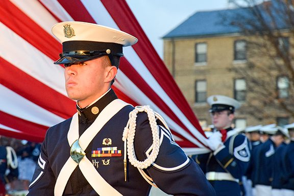 A cadet stands in front of an American flag.