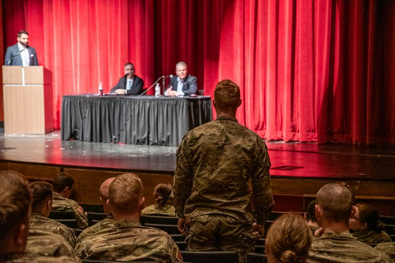 A cadet asks a question during a panel discussion with two businessmen.