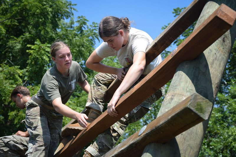 An O-Course Committee cadet shows another cadet the best way to travel an obstacle.