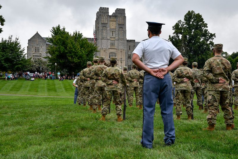 A company of cadets marches past spectators on the Drillfield.